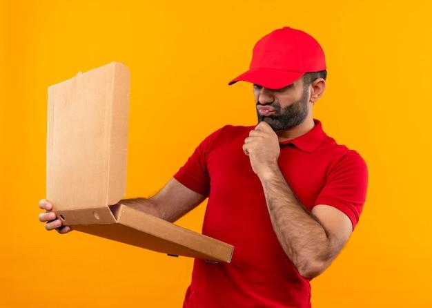 Bebaarde bezorger in rood uniform en pet die open pizzadoos vasthoudt en er verward en erg angstig naar kijkt terwijl hij over oranje muur staat
