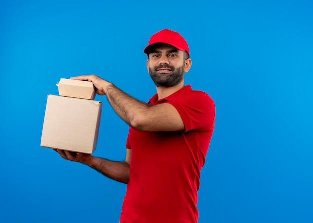 Bebaarde bezorger in rood uniform en pet met doos pakketten met zelfverzekerde glimlach staande over blauwe muur