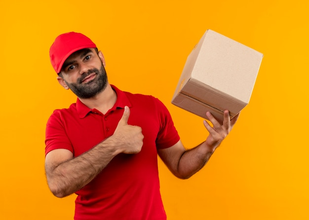 Bebaarde bezorger in rood uniform en pet met doospakket met duimen omhoog positief en gelukkig staande over oranje muur