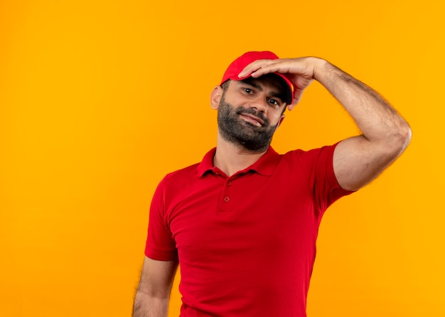 Bebaarde bezorger in rood uniform en pet met hand op zijn camera glimlachend staande over oranje muur