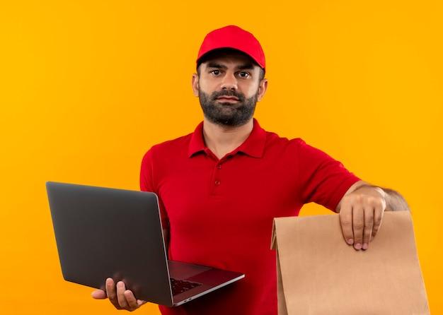 Bebaarde bezorger in rood uniform en pet met papieren pakket en laptop met ernstig gezicht staande over oranje muur