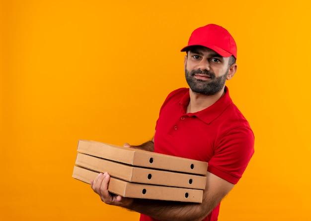 Bebaarde bezorger in rood uniform en pet met stapel pizzadozen die zelfverzekerd over oranje muur staan kijken