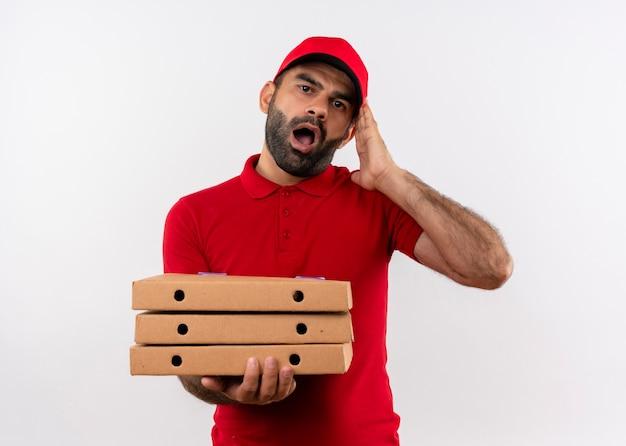 Bebaarde bezorger in rood uniform en pet met stapel pizzadozen geschokt en verward met wijd open mond staande over witte muur