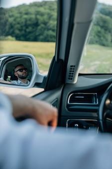 Bebaarde blanke zakenman die met kop en schouders naar de camera kijkt door de achteruitkijkspiegel rear