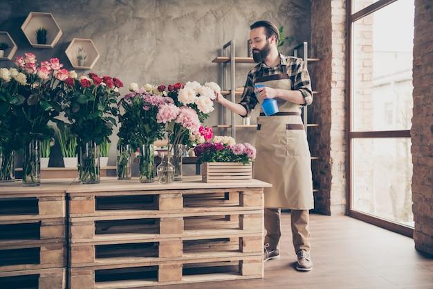 Bebaarde bloemist die in zijn bloemenwinkel werkt