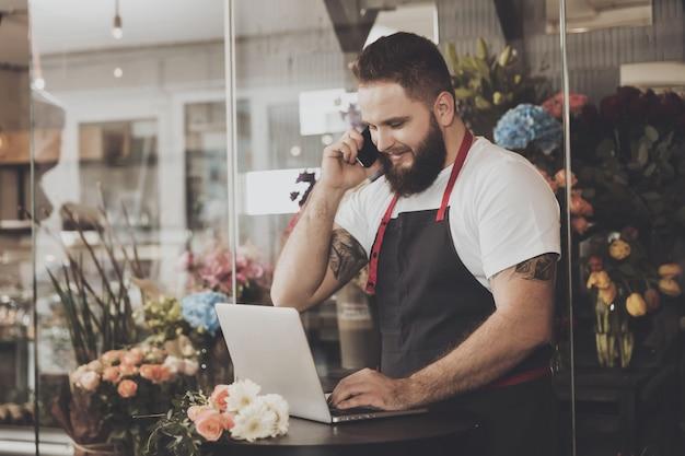 Bebaarde bloemist neemt een bestelling via de mobiele telefoon