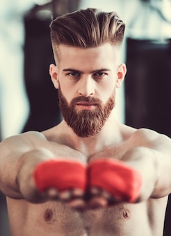 Bebaarde bokser met blote torso kijkt naar de camera.