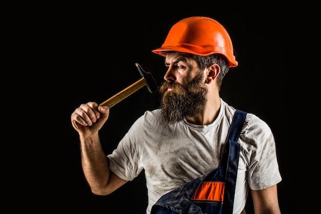 Bebaarde bouwer die op zwarte achtergrond wordt geïsoleerd. hamer hameren. bouwer in helm, hamer, klusjesman, bouwvakker in bouwvakker. bebaarde man werknemer met baard