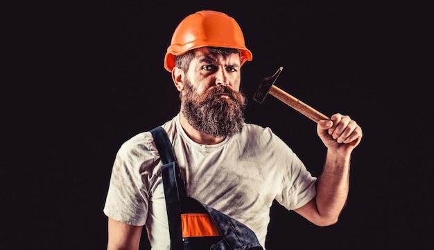 Bebaarde bouwer die op zwarte muur wordt geïsoleerd. hamer hameren. bouwer in helm, hamer, klusjesman, bouwvakker in bouwvakker.