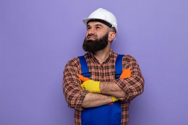 Bebaarde bouwer man in bouw uniform en veiligheidshelm dragen rubberen handschoenen opzoeken met glimlach op gezicht blij en zelfverzekerd met armen gekruist op zijn borst staande over paarse achtergrond