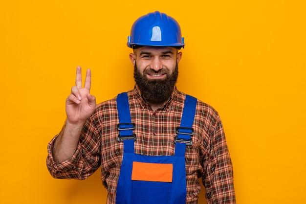 Bebaarde bouwer man in bouw uniform en veiligheidshelm kijken camera blij en positief tonen v-teken glimlachend staande over oranje achtergrond