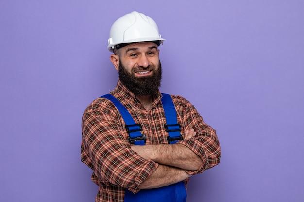 Bebaarde bouwer man in bouw uniform en veiligheidshelm kijken camera vrolijk glimlachend met armen gekruist op borst staande over paarse achtergrond