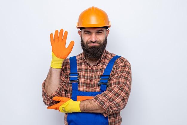 Bebaarde bouwer man in bouw uniform en veiligheidshelm met rubberen handschoenen kijkend naar camera glimlachend vrolijk zwaaiend met hand staande op witte achtergrond