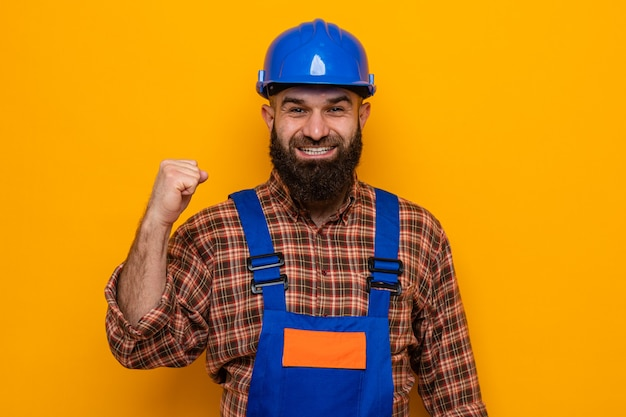 Bebaarde bouwer man in bouwuniform en veiligheidshelm kijkend naar camera blij en opgewonden gebalde vuist glimlachend vrolijk staande over oranje achtergrond
