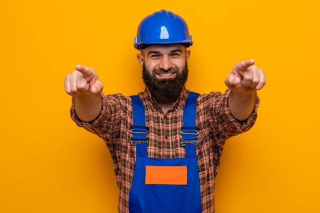 Bebaarde bouwer man in constructie uniform en veiligheidshelm wijzend met wijsvingers naar camera glimlachend vrolijk staande over oranje achtergrond