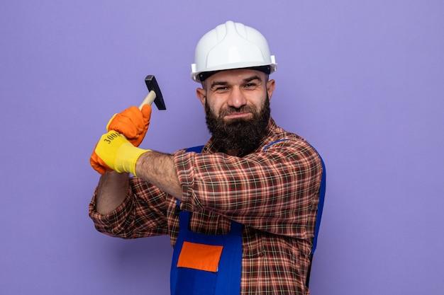 Bebaarde bouwersmens in bouwuniform en veiligheidshelm die een hamer slingeren die camera glimlachen die zich over purpere achtergrond bekijken
