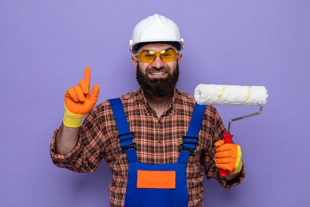 Bebaarde bouwersmens in bouwuniform en veiligheidshelm die rubberhandschoenen dragen die verfroller glimlachen die vrolijk toont wijsvinger met nieuw idee