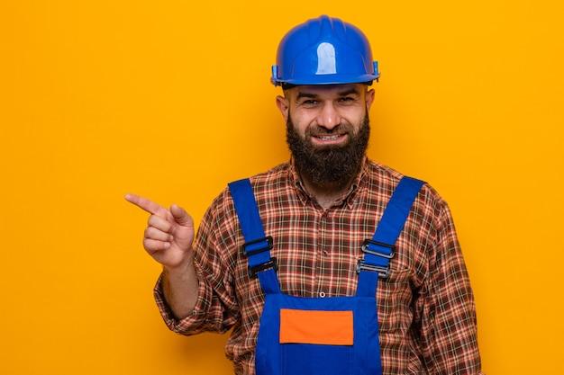 Bebaarde bouwman in bouwuniform en veiligheidshelm die er gelukkig en positief uitziet, wijzend met de wijsvinger naar de zijkant glimlachend