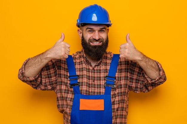 Bebaarde bouwman in bouwuniform en veiligheidshelm die er gelukkig en vrolijk uitziet met duimen omhoog
