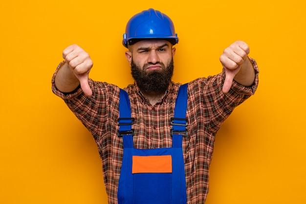 Bebaarde bouwman in bouwuniform en veiligheidshelm die er ontevreden uitziet met duimen naar beneden