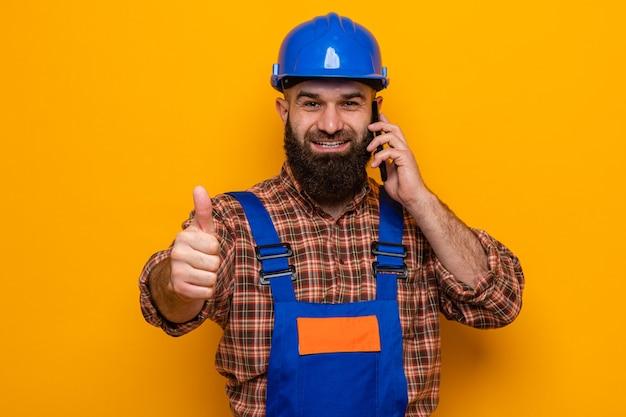 Bebaarde bouwman in bouwuniform en veiligheidshelm die er vrolijk glimlachend uitziet en duimen omhoog laat zien