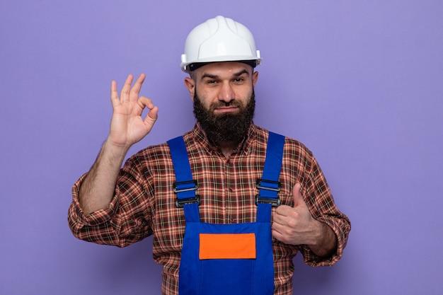 Bebaarde bouwman in bouwuniform en veiligheidshelm die glimlachend vrolijk lacht en een goed teken doet met duimen omhoog