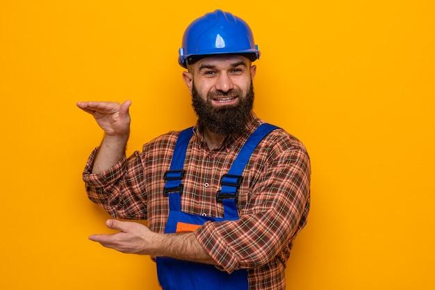 Bebaarde bouwman in bouwuniform en veiligheidshelm die glimlachend vrolijk lacht en maatgebaar met handen toont