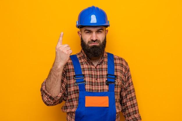 Bebaarde bouwman in bouwuniform en veiligheidshelm die kijkt met een serieus gezicht met wijsvinger nummer één