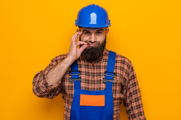 Bebaarde bouwman in bouwuniform en veiligheidshelm die met een serieus gezicht kijkt en een stiltegebaar maakt zoals het sluiten van de mond met een rits