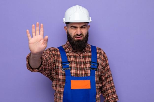 Bebaarde bouwman in bouwuniform en veiligheidshelm die met een serieus gezicht kijkt en een stopgebaar maakt met de hand