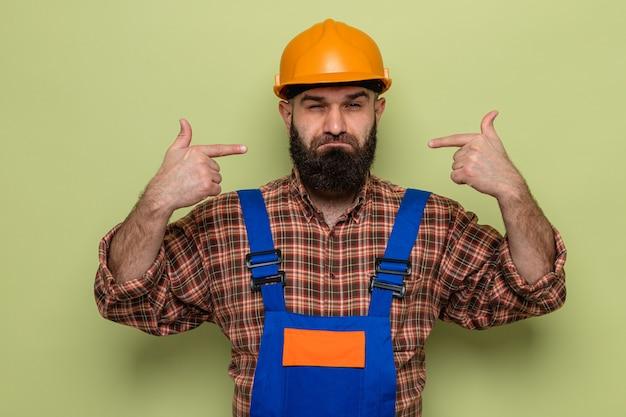 Bebaarde bouwman in bouwuniform en veiligheidshelm die met zelfverzekerde uitdrukking naar zichzelf wijst