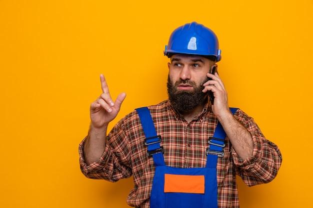 Bebaarde bouwman in bouwuniform en veiligheidshelm die opzij kijkt met een serieus gezicht met wijsvinger terwijl hij op mobiele telefoon praat