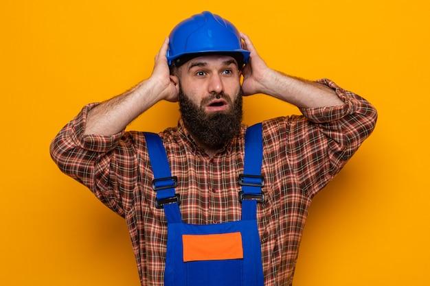 Bebaarde bouwman in bouwuniform en veiligheidshelm die opzij kijkt, verward en bezorgd, hand in hand op zijn hoofd