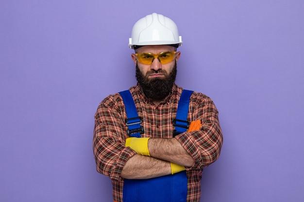 Bebaarde bouwman in bouwuniform en veiligheidshelm die rubberen handschoenen draagt en kijkt met een serieus fronsend gezicht met gekruiste armen arms