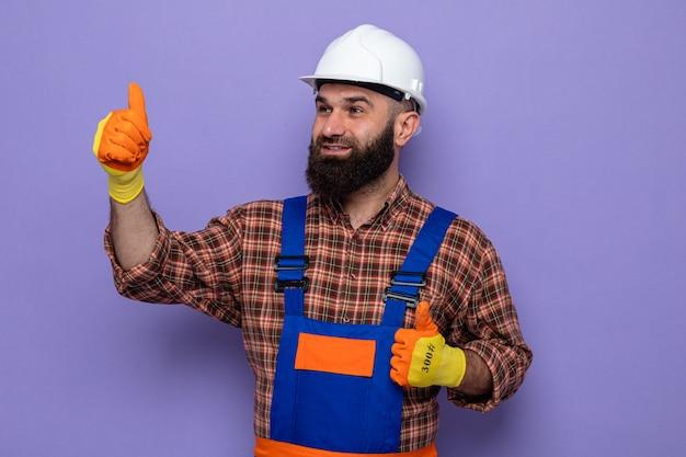 Bebaarde bouwman in bouwuniform en veiligheidshelm die rubberen handschoenen draagt en opzij kijkt, gelukkig en opgewekt met duimen omhoog glimlachend