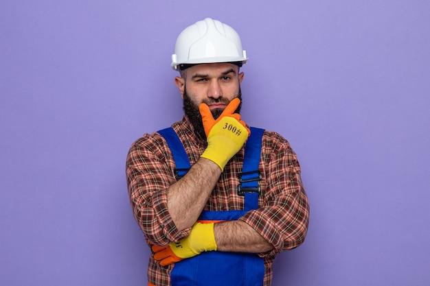 Bebaarde bouwman in bouwuniform en veiligheidshelm die rubberen handschoenen draagt, kijkend met de hand op zijn kin denkend