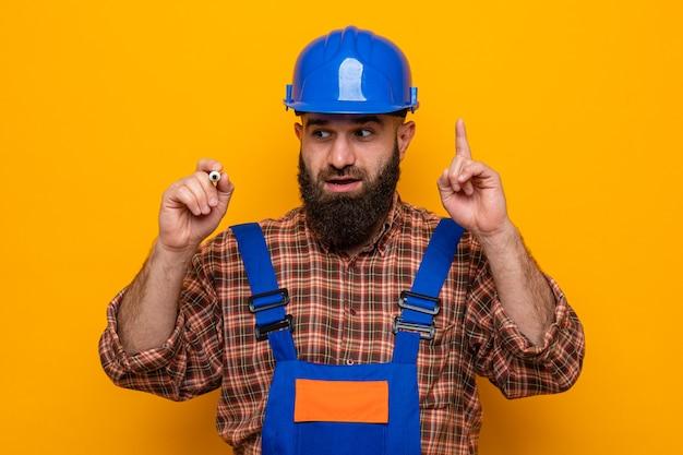 Bebaarde bouwman in bouwuniform en veiligheidshelm die verrast en gelukkig kijkt met pen in de lucht