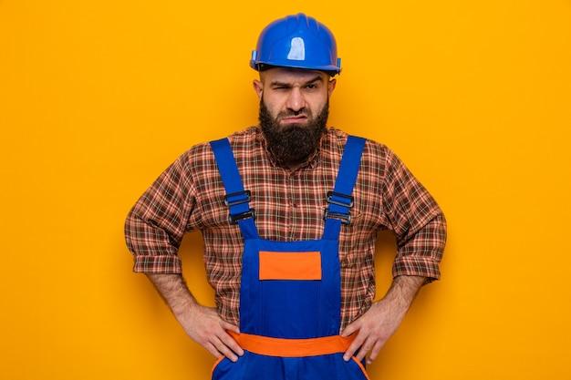 Bebaarde bouwman in bouwuniform en veiligheidshelm kijkend met boos gezicht met armen op heup