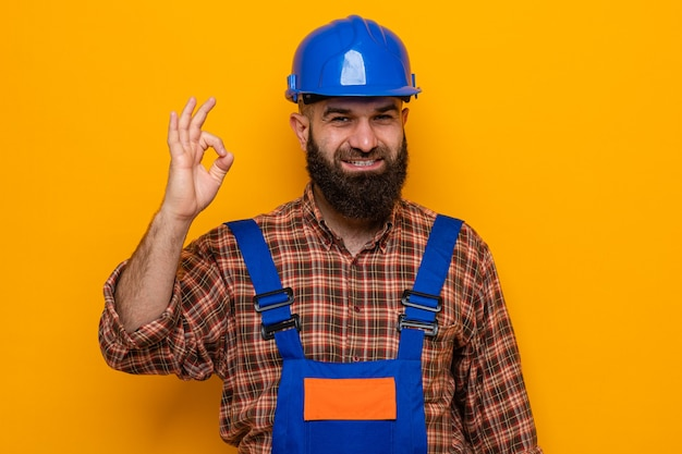 Bebaarde bouwman in bouwuniform en veiligheidshelm kijkend naar camera glimlachend vrolijk doend ok teken staande over oranje achtergrond