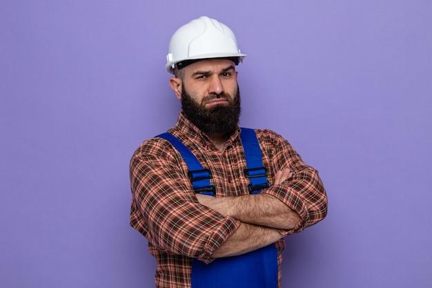 Bebaarde bouwman in bouwuniform en veiligheidshelm kijkend naar camera met serieus gezicht met gekruiste armen op borst over paarse achtergrond