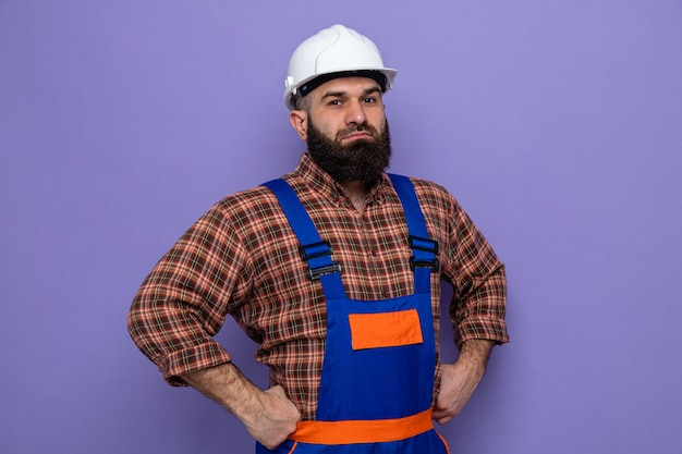 Bebaarde bouwman in bouwuniform en veiligheidshelm kijkend naar camera met zelfverzekerde uitdrukking met handen op heup over paarse achtergrond