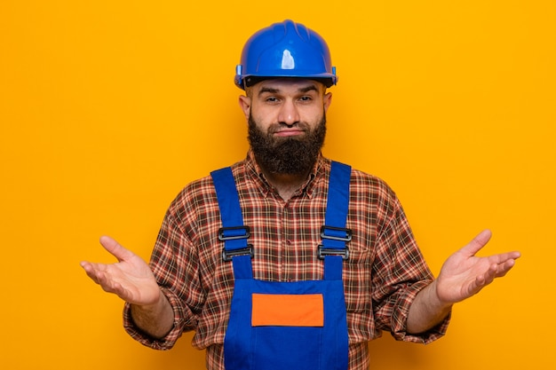 Bebaarde bouwman in bouwuniform en veiligheidshelm kijkend naar camera verward spreidende armen naar de zijkanten staande over oranje achtergrond