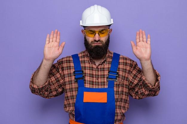 Bebaarde bouwman in bouwuniform en veiligheidshelm met een gele veiligheidsbril die er zelfverzekerd uitziet met opgeheven armen over een paarse achtergrond