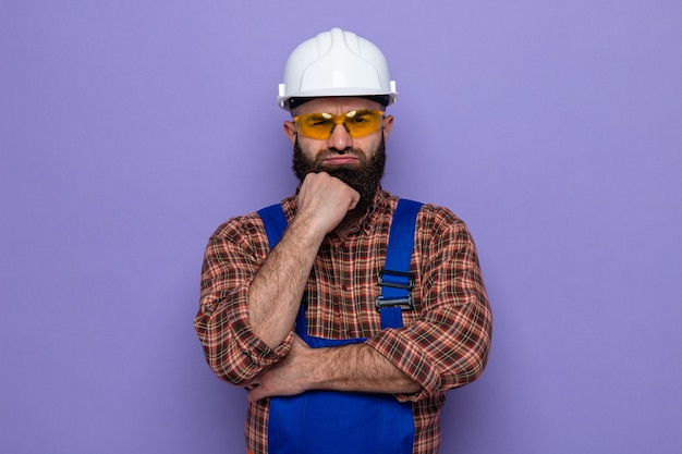 Bebaarde bouwman in bouwuniform en veiligheidshelm met een gele veiligheidsbril die met de hand op zijn kin kijkt met een boos gezicht