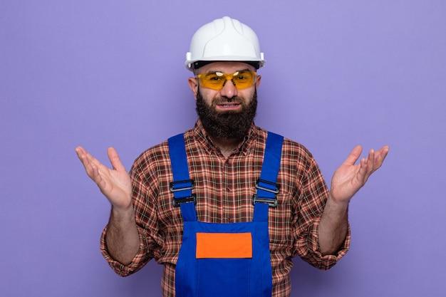 Bebaarde bouwman in bouwuniform en veiligheidshelm met een gele veiligheidsbril die naar de camera kijkt en glimlachend vrolijk zijn armen opheft die over een paarse achtergrond staan