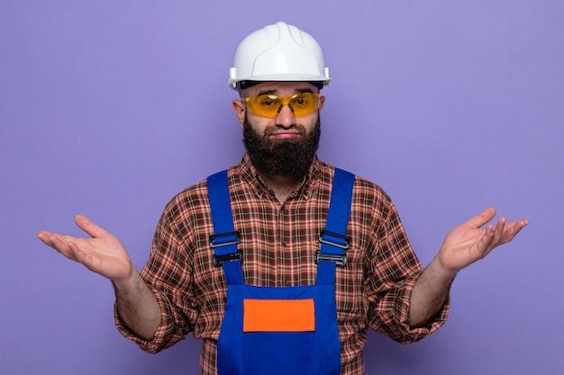 Bebaarde bouwman in bouwuniform en veiligheidshelm met gele veiligheidsbril kijkend naar camera verward spreidende armen naar de zijkanten zonder antwoord over paarse achtergrond