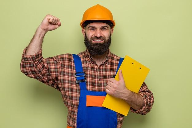 Bebaarde bouwman in bouwuniform en veiligheidshelm met klembord die er blij en opgewonden uitziet en zijn vuist opsteekt