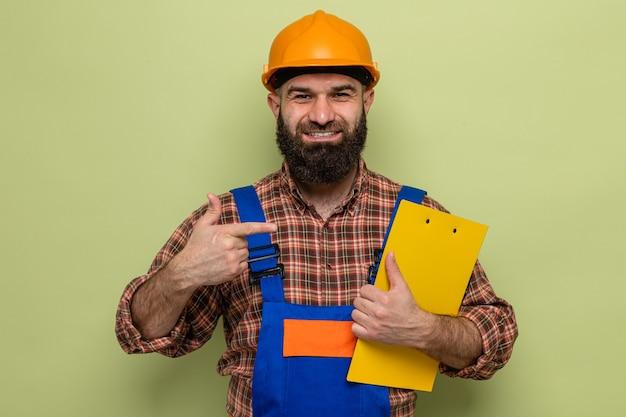 Bebaarde bouwman in bouwuniform en veiligheidshelm met klembord wijzend met wijsvinger erop gelukkig en zelfverzekerd glimlachend