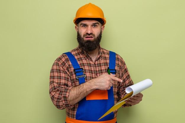 Bebaarde bouwman in bouwuniform en veiligheidshelm met klembord wijzend met wijsvinger naar verward over groene achtergrond