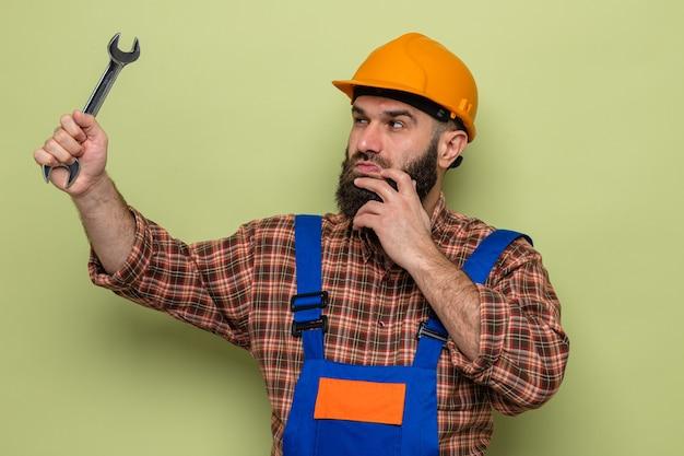 Bebaarde bouwman in bouwuniform en veiligheidshelm met moersleutel die ernaar kijkt en geïntrigeerd staat over groene achtergrond